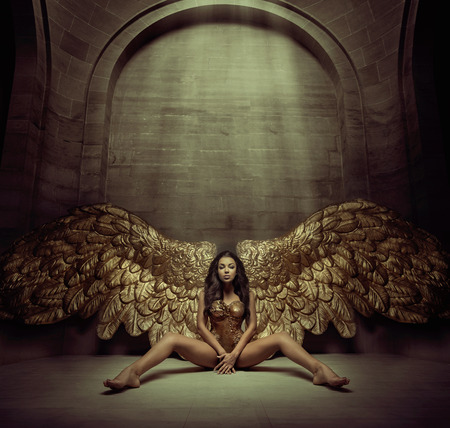 Photo pour Alluring gold angel in the dark hall - image libre de droit