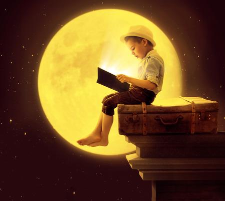 Photo pour Cute little kid reading a book in the moon light - image libre de droit