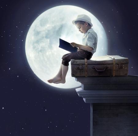 Photo pour Portrait of a little boy reading a fairy tale - image libre de droit