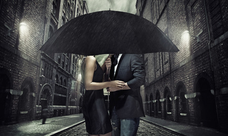 Adorable couple under the black umbrellaの写真素材