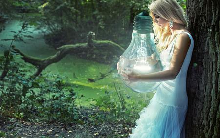 Photo pour Stunning blond woman holding huge lightbulb - image libre de droit