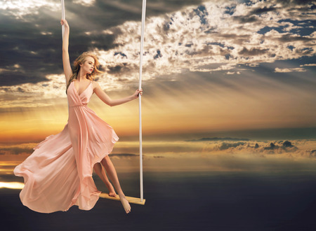 Photo pour Attractive young woman on a swing above the sea - image libre de droit