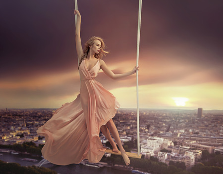 Adorable woman dangling above the city