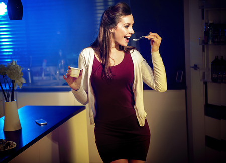 Young fit woman eating yoghurt