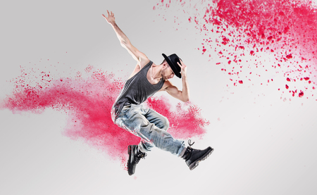 Portrait of a dancer excercising among a colorful powder