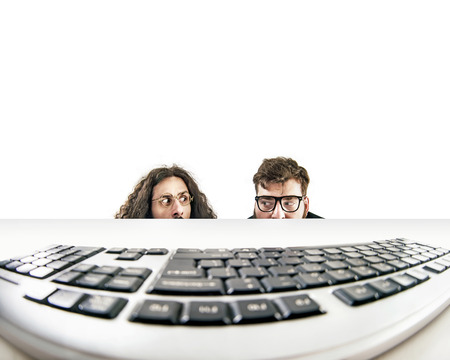 Photo pour Two funny nerds staring at a keyboard - image libre de droit