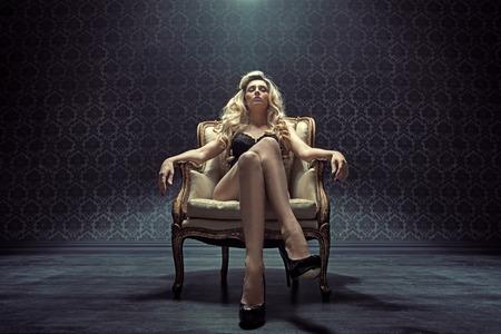 Photo pour Dominating blond woman sitting on the vintage armchair - image libre de droit
