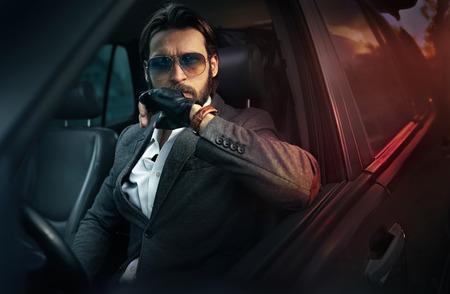 Photo pour Handsome fashion man driving a car - image libre de droit