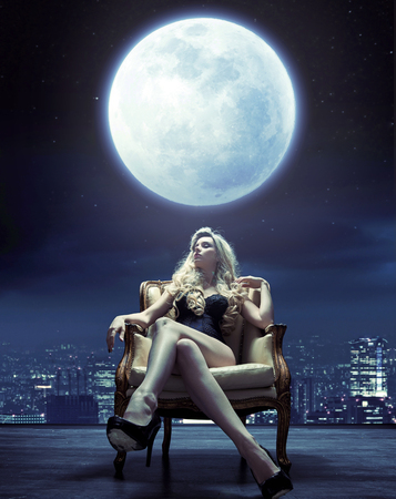 Sensual young woman relaxing under the moon lightの写真素材
