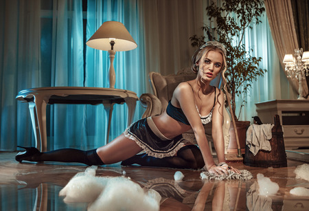 Photo for Sexy blond maid cleaning floor in the stylish apartment - Royalty Free Image
