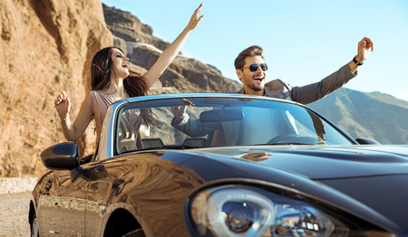 Foto de Smart, relaxed couple riding a luxurious convertible - Imagen libre de derechos