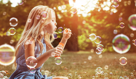 Photo for Portrait of a cheerful child blowing soap bubbles - Royalty Free Image