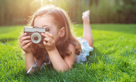 Photo for Cute little childl lying on green lawn and taking a picture - Royalty Free Image