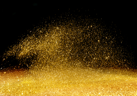 Photo for Golden, shining powder scattered over the dark background - Royalty Free Image