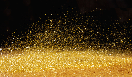 Photo pour Golden, shining powder scattered over the dark background - image libre de droit