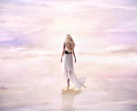 Photo pour Conceptual picture of a blond woman walking on the delicate, fluffy clouds - image libre de droit