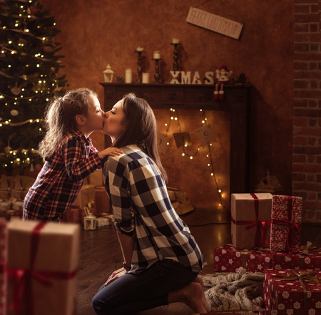 Foto de Conceptual portrait of a mother kissing a little daughter, christmas items in background - Imagen libre de derechos