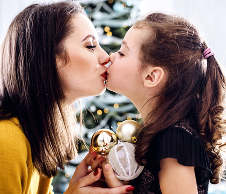Foto de Portrait of a brunette mother kissing her daughter holding glass balls - Imagen libre de derechos