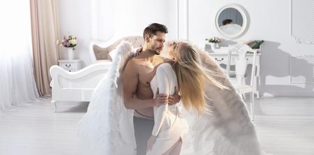 Photo pour Conceptual portrait of an archangel embracing a beautiful, blond woman - image libre de droit