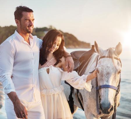 Photo pour Young couple walking a majestic, white horse - seaside landscape - image libre de droit