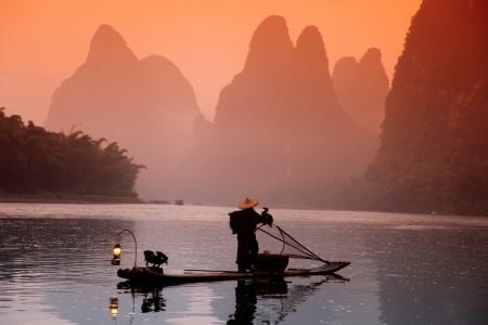 Chinese man fishing with cormorants birds, Yangshuo, Guangxi region, traditional fishing use trained cormorants to fish