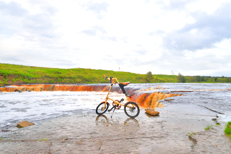 ULYANOVKA, RUSSIA - 26 AUGUST 2016: Bicycle Strida on coast of river. Strida - folding bike with a memorable frame in the shape of the letter A.