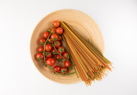 Bowl with raw pasta and tomatoes isolated on white background, top view. Flat lay