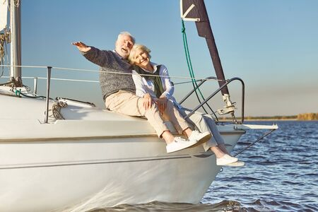 Photo pour Anchors away. Happy senior couple hugging on sail boat or yacht deck floating in sea. Man hugging his woman while enjoying the view - image libre de droit