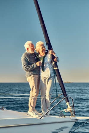 Photo pour Full leghth of beautiful happy senior couple in love, retired man and woman standing on the side of sail boat floating in sea, hugging and enjoying view - image libre de droit