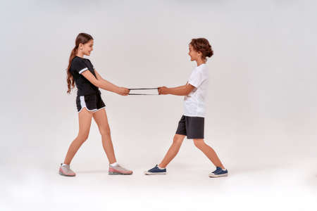 Photo for Full-length shot of happy teenage boy and girl having fun while exercising with resistance band, standing isolated over grey background - Royalty Free Image