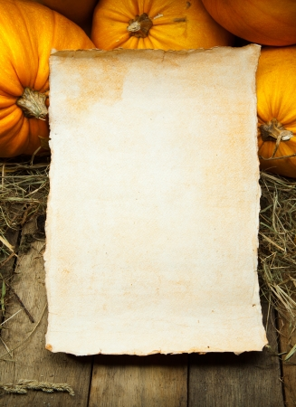 orange pumpkins and  sheet of paper on wooden background