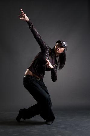 beautiful brunette dancing against dark background