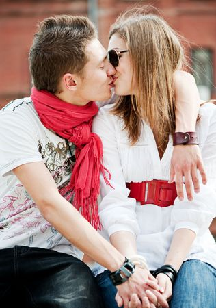 young trendy couple in love kissing each other