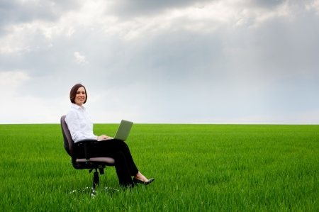 businesswoman with laptop sitting on recliner over green meadowの写真素材