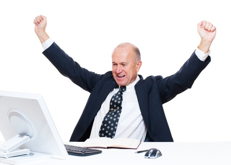 senior happy businessman sitting in workplace and raising hands up