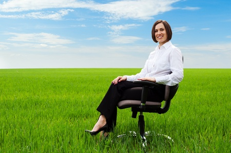 happy businesswoman sitting on chair over green field