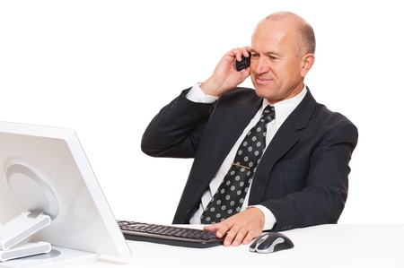 smiley businessman sitting at desk in office and talking on mobile phone