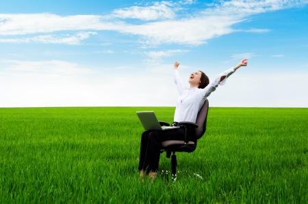 Foto de happy businesswoman with computer sitting on chair over green field  - Imagen libre de derechos