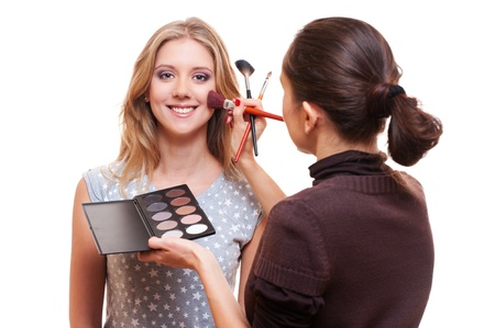 professional make-up artist working with model. studio picture over white