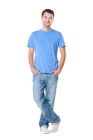 smiley young man in blue t-shirt and jeans standing with hands in pocket