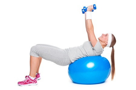 attractive woman doing exercises with ball and dumbbells. isolated on white background