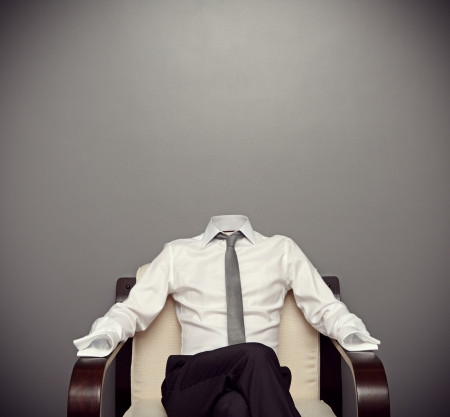 invisible man in formal wear sitting on armchair against grey background