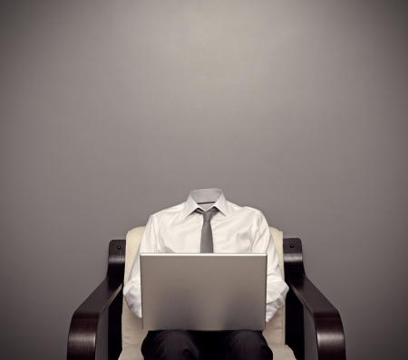 invisible man in formal wear sitting on chair and working with laptop against grey background