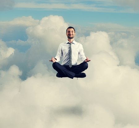 happy businessman in formal wear meditating in the sky