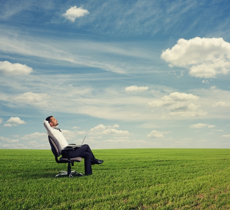 smiley businessman resting on the green field