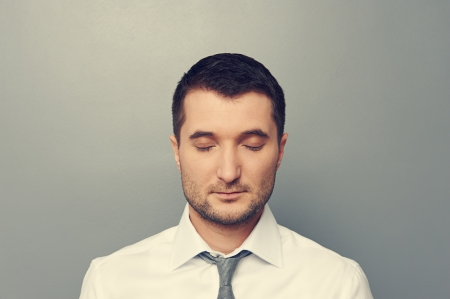 portrait of businessman with closed eyes over grey background