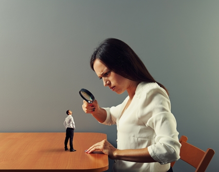 serious businesswoman looking with magnifying glass at small man
