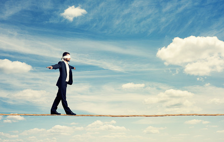man with the blindfold walking on the rope over blue sky