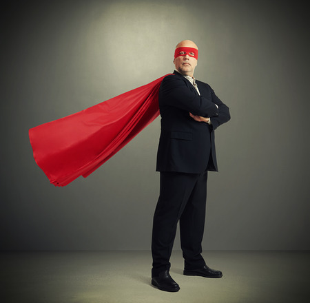 Photo pour senior businessman dressed as a superhero in red mask and cloak over dark grey background - image libre de droit