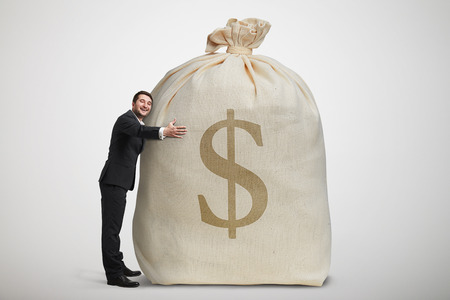 happy man embracing big bag with money over light grey background